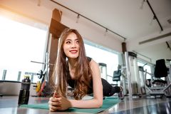 Asian woman exercising in the gym. Young woman workout in fitness for her healthy and office girl lifestyle. She is planking beside the protein shake bottle Royalty Free Stock Images