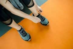 Asian woman exercising in the gym. Young woman workout in fitness for her healthy and office girl lifestyle. She was tying her shoes tightly Royalty Free Stock Photography