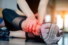 Asian woman exercising in the gym. Young woman workout in fitness for her healthy and office girl lifestyle. Her ankle injury from exercise Stock Images