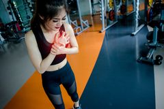 Asian woman exercising in the gym. Young woman workout in fitness for her healthy and office girl lifestyle. Her chest injury from exercise Stock Photos