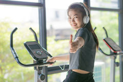 Asian woman exercising at the gym on a cross trainer Royalty Free Stock Images