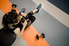 Asian woman exercising in the gym. Young woman workout in fitness for her healthy and office girl lifestyle. She is drinking a protein shake Royalty Free Stock Image