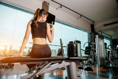 Asian woman exercising in the gym. Young woman workout in fitness for her healthy and office girl lifestyle. She is drinking a protein shake Royalty Free Stock Photo