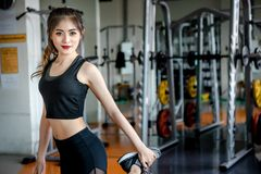 Asian woman exercising in the gym. Asian woman exercising in the gym, Young woman workout in fitness for her healthy and office girl lifestyle Stock Image