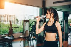 Asian woman exercising in the gym. Young woman workout in fitness for her healthy and office girl lifestyle. She is drinking fresh water Royalty Free Stock Photos