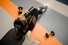 Asian woman exercising in the gym,. Young woman workout in fitness for her healthy and office girl lifestyle. she is drinking a protein shake Stock Photo