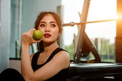 Asian woman exercising in the gym,. Young woman workout in fitness for her healthy and office girl lifestyle. She is eating an apple Stock Photo