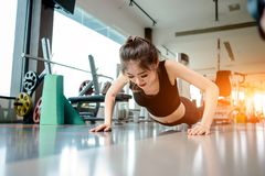 Asian woman exercising in the gym. Young woman workout in fitness for her healthy and office girl lifestyle. She is planking beside the protein shake bottle Stock Photos