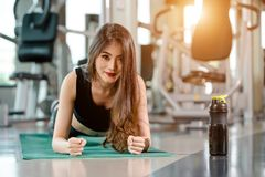 Asian woman exercising in the gym. Young woman workout in fitness for her healthy and office girl lifestyle. She is planking beside the protein shake bottle Royalty Free Stock Photo