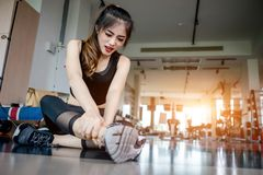 Asian woman exercising in the gym. Young woman workout in fitness for her healthy and office girl lifestyle. Her right ankle injury from exercise Royalty Free Stock Photo