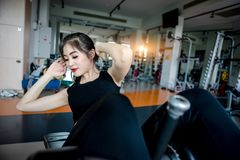 Asian woman exercising in the gym. Young woman workout in fitness for her healthy and office girl lifestyle. She is sit up position Royalty Free Stock Images