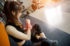 Asian woman exercising in the gym. Young woman workout in fitness for her healthy and office girl lifestyle. Her wrist injury from exercise Royalty Free Stock Photo