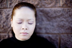 Asian woman eyes closed. An Asian woman standing outside with her eyes clothes in a thinking mood as she ponders something against a brick wall Royalty Free Stock Images