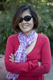 Asian woman with eyes glasses in red shirt smiling in the park Royalty Free Stock Photo