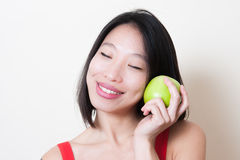 Asian woman face smiling with closed eyes with green apple Royalty Free Stock Photos