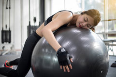 Asian Woman falling asleep after doing exercises in the gym. Fit stock image