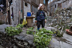 Asian woman farmer Miao people, stands in courtyard peasant hous Stock Photo