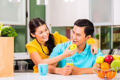 Asian woman feeding boyfriend with apple Stock Images