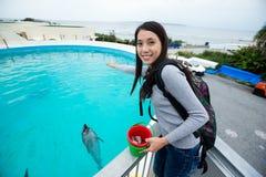 Asian Woman feeding dolphin in aquarium Stock Photo