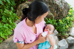 Asian woman feeding her baby in park from top Stock Photos