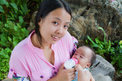 Asian woman feeding her baby and smile Royalty Free Stock Photos