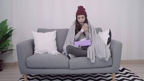 Asian woman feel headache wrapped in grey blanket blow the nose and use tissue while lying on couch when relax in living room. Asian woman feel headache wrapped stock video