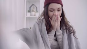 Asian woman feel headache wrapped in grey blanket blow the nose and use tissue while lying on couch when relax in living room. Asian woman feel headache wrapped stock footage