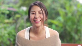 Asian woman feeling happy smiling and looking to camera while relax on table in garden at home in the morning. Lifestyle women