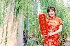 Asian women in festive costumes showing red couplets with chinese royalty free stock photos