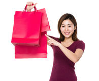 Asian woman finger point to shopping bag Royalty Free Stock Images
