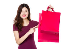 Asian woman with finger point to shopping bag Stock Photography