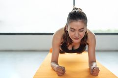 Asian woman fitness girl do plank at fitness gym on yoga mat. He. Althcare and Healthy concept. Training and Body build up theme. Strength and Beauty concept stock photography