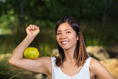 Asian woman flexing her muscle with a mango Royalty Free Stock Photo