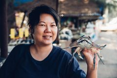 Asian woman and flower crab at Thai seafood market. Asian woman plump body holding a fresh raw sea flower crab & x28;portunus pelagicus& x29; premium grade Royalty Free Stock Images