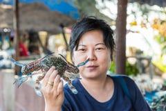 Asian woman and flower crab at Thai seafood market. Asian woman plump body holding a fresh raw sea flower crab & x28;portunus pelagicus& x29; premium grade Stock Images