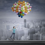 Asian woman flying with balloons Stock Photo