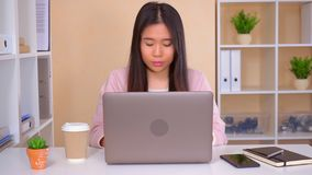 Worker shows sign quiet in the office. Asian woman focused at work. businesswoman using laptop looking at the camera showing hand gesture silence stock video
