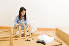 Asian woman follow instruction for assembling chair. At home stock photography