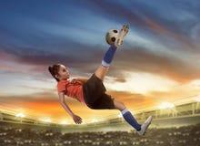 Asian woman football player kick ball Stock Photo