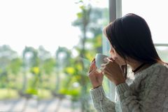Asian woman fresh morning drinking coffee and looking out of the window on sunny day. Copy Space.  Lifestyle Concept Stock Images