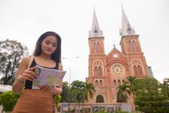 Asian woman in front of Notre Dame Cathedral in Ho Chi Minh City. Portrait of young beautiful Asian tourist woman exploring Ho Chi Minh city in Vietnam royalty free stock photos