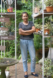 Asian woman gardener cross one's arm and smiling at her garden Royalty Free Stock Photo