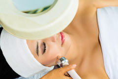 Asian woman getting a facial treatment in spa Stock Images