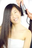 Asian woman getting hair straightened happy Royalty Free Stock Image