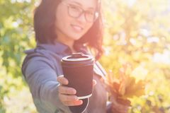 Asian woman giving hot coffee to camera royalty free stock photos