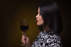 Asian woman with glass of red wine Stock Photography