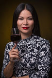 Asian woman with glass of red wine. Portrait of asian woman in traditional dress demonstrating expensive red wine in a glass. Black-haired lady with red lips royalty free stock image