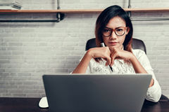 Asian woman with glasses and his pen ready to work. Focus on fac Royalty Free Stock Images