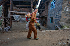 Asian woman goes on rural Street, carrying baby on back. Stock Photos
