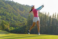 Asian woman golf player doing golf swing tee off on the green evening time, she presumably does exercise. royalty free stock images